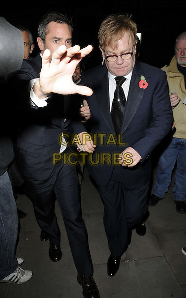 minder & Sir Elton John .The George Michael special concert, Royal Opera House, Covent Garden, London, England..November 6th, 2011.full length black suit poppy glasses hand blocking bodyguard .CAP/CAN.©Can Nguyen/Capital Pictures.