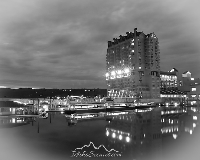 Idaho, North, Coeur d'Alene. The Coeur d'Alene Resort and Tour boats reflects in the calm water of  Lake Coeur d'Alene at night.