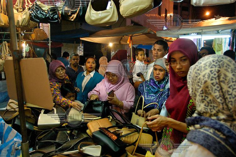 Women in headscarves shopping at downtown Saturday night Pasar Malam (night market) close to Little India and Jalan Tunku Abdul Rahman.
