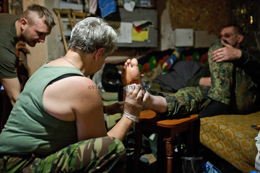 UKRAINE, Pisky: Mama is taking care of soldier who has walked on a sharp object during a demining mission. <br /> <br /> UKRAINE, Pisky: Mama prend soin d'un soldat qui a march&eacute; sur un objet pointu au cours d'une mission de d&eacute;minage.