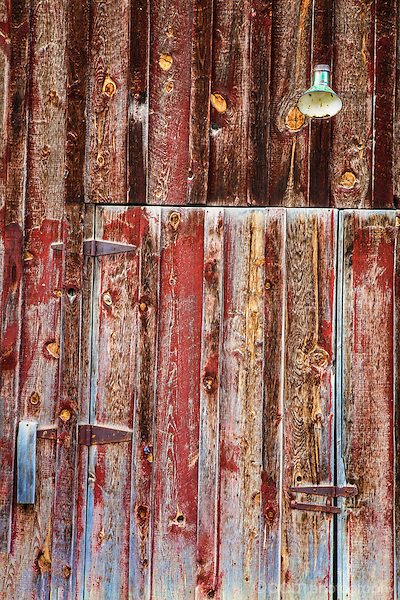 Close-up of old wooden red door with single light