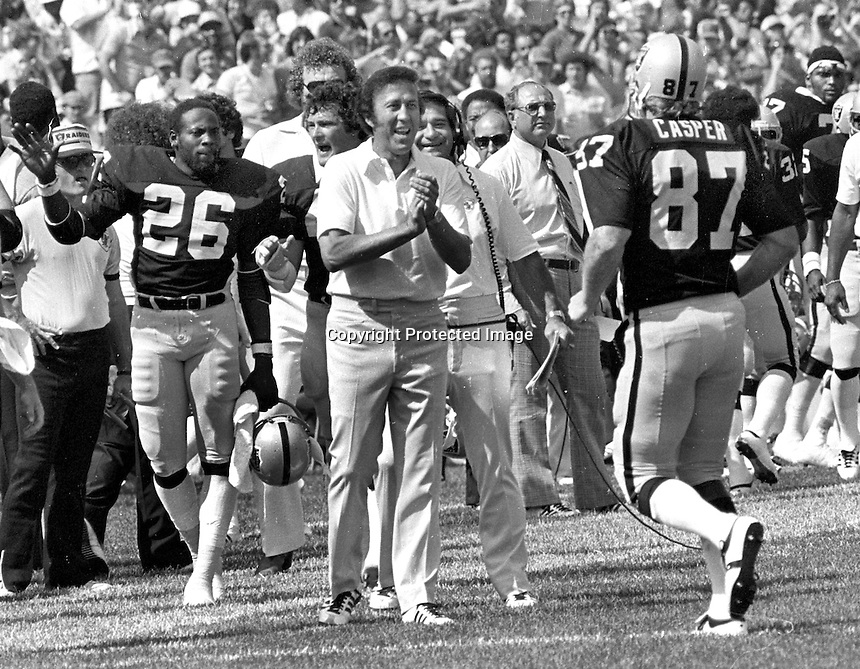 Raider Dave Casper is greeted by coach Tom Flores and the Raider bench after TD grab. (1979 photo by Ron Riesterer)