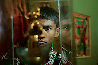 Mohammad Sharif looks at a trophy he won for a local cricket match in Chittagong, Bangladesh.