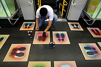 MEDELLÍN, COLOMBIA-MAY 4: A urban artists make footprints with aerosol, so that passengers know where they should be on a train during the pandemic, COVID-19. on May 4, 2020, in Medellín, Colombia. The physical distance and the maximum occupancy of 35% of the public transport system, a requirement of the National Government, as a preventive measure to stop the spread of COVID-19 (Photo by Fredy Builes/VIEWpress)