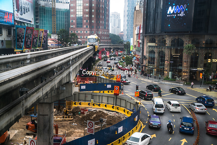 A monorail approaches while traffic weaves through a construction site in downtown Kuala Lumpur, Malaysia.