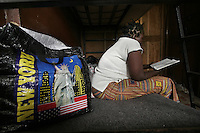 "Life in City of Rest is in stark contrast to the symbol of freedom on this bag. A girl sits in a room she shares with the other girls and reads a bible...City Of Rest is, according to a sign over the entrance, a ""counselling & mini-rehabilitation centre for drug addicts, alcoholics, traumatised and delinquent youths"".  It is the only place in Sierra Leone to offer any rehabilitation for these people. Though the methods used may be seen as unusual by western standards, the pastor in charge claims increasing success. The treatment consist of chaining the youths to chairs, prayers, plenty of food and rest. © Fredrik Naumann Freetown, Sierra Leone."