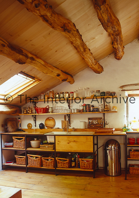 The pitched kitchen ceiling is supported by massive old wooden beams and panelled with tongue and groove