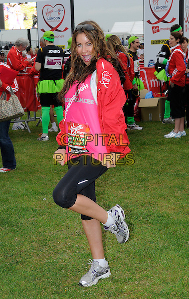 JO EMMA LARVIN.Celebrities take part in the Virgin London Marathon 2010, London, England, UK, 25th April 2010..full  length pink red top black leggings trainers one leg standing on foot mouth open funny cropped .CAP/DH.©David Hitchens/Capital Pictures.