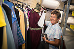 © Joel Goodman - 07973 332324 . 28 August 2013 . Wood Street Mission , Manchester , UK . Volunteer Wendy Witts (70 from Kearsley) (correct) shows some of the donated clothes on the rack in the basement . Photo credit : Joel Goodman