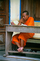 Local Buddhist monk wearing traditional orange robe studying outside a temple. Chiang Mai - Northern Thailand.