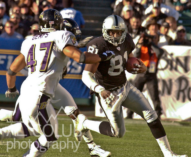 Baltimore Ravens defensive back Will Demps (47) attempts to stop Oakland Raiders wide receiver Tim Brown (81) on Sunday, December 12, 2003, in Oakland, California. The Raiders defeated the Ravens 20-12.