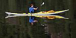 A woman kayaks along the still waters at the end of Princess Louisa inlet along the coast of British Columbia.