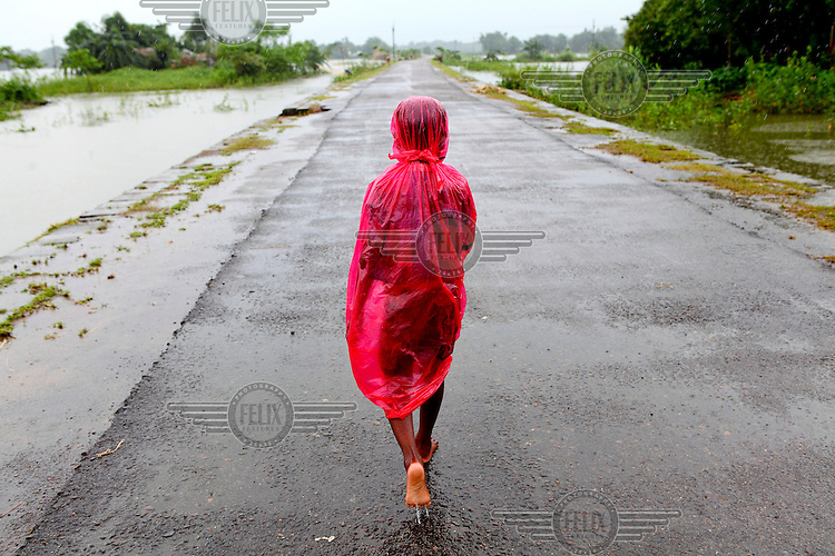 Six year old Nayan walks along the only path in Sunamganj which isn't submerged by floodwaters during a monsoon.