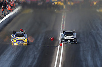 Feb. 24, 2013; Chandler, AZ, USA; NHRA funny car driver Ron Capps (left) races alongside Cruz Pedregon who hits the centerline timing blocks during the Arizona Nationals at Firebird International Raceway. Mandatory Credit: Mark J. Rebilas-
