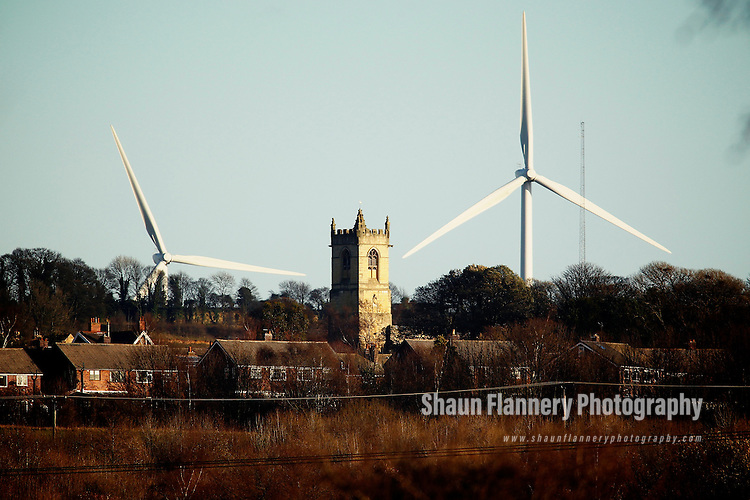 Pix: Shaun Flannery/shaunflanneryphotography.com...COPYRIGHT PICTURE>>SHAUN FLANNERY>01302-570814>>07778315553>>..14th December 2011……………Wind Farm at Marr, nr. Doncaster - 2 huge Wind Turbines tower above St Peter Church, Barnburgh, South Yorkshire.
