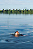 Xingu Indigenous Park, Mato Grosso State, Brazil. Aldeia Tres Irmaos (Kaiabi); child enjoying a swim in the river.