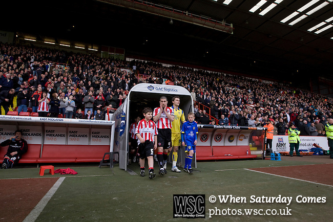Sheffield United 2 Leeds United 0, 19/03/2011. Bramall Lane, Championship. Sheffield United captain Nick Montgomery (stripes) leading his players out on to the pitch at the club's Bramall Lane ground prior to the Npower Championship fixture against Leeds United. The home team won the game by two goals to nil watched by a crowd of 23,728. Bramall Lane is the world's oldest professional football ground and at one time hosted both football and cricket. Photo by Colin McPherson.