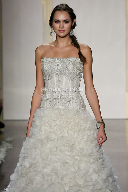 Model walks runway in an ivory shear lace corseted bodice with beaded and embroidered overlay, strapless curved neckline, droppped waist, lavishly textured tulle and organza A-line skirt, chapel train wedding dress by Lazaro Perez, from the Lazaro Spring 2012 Bridal fashion show.
