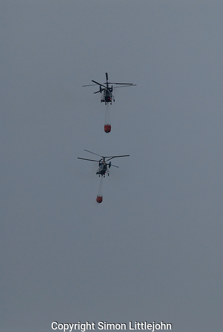 Two Kamov twin rotor helicopters with water balloons suspended in flight, fighting forest fire near Estepona, Costa del Sol, Andalucia, Spain.