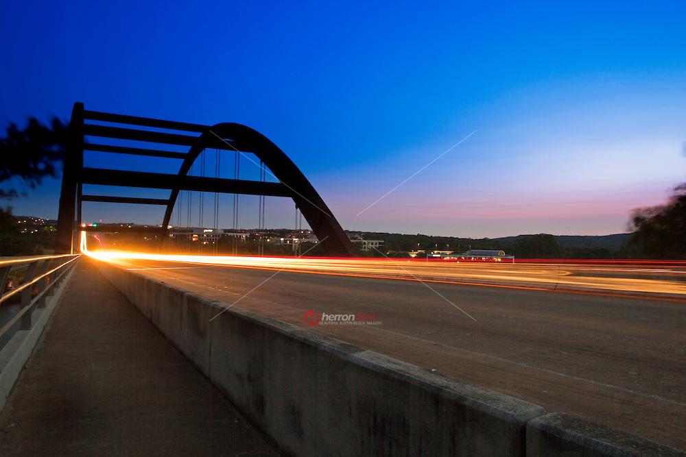 Car lights leave streaks as the pass through the 360 Pennybacker bridge in Austin, Texas