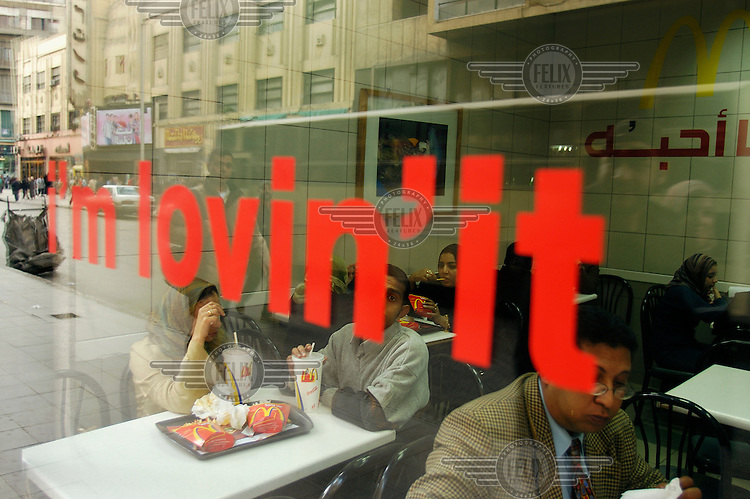 "People eating in McDonalds fast food restaurant with global advertising slogan in English ""I'm Lovin' it"" across window."
