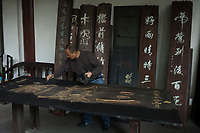 "Meishan, Sichuan province, China, October 2014 - A worker renovates a plaque inside the Three Su Temple which was built to commemorate famous Song dynasty poet and politician Su Dongpo and his father and brother who were also notable writers (the ""three Su""). Su Dongpo was native of Meishan."