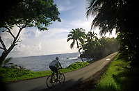 Man biking along thee coastline in the Kapoho area, Big Island