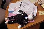 Voodoo doll lying on a desk in an office dressed as a business man in a black suit and blue tie with pins stuck in his body