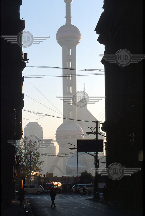 View of the Oriental Pearl TV Tower from across the Huangpu river, silhouetted by old colonial buildings on the Bund.