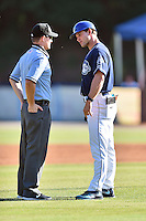 Asheville Tourists manager Warren Schaeffer (13) discusses a disputed call with umpire Sam Burch during a game against the Charleston RiverDogs at McCormick Field on July 9, 2016 in Asheville, North Carolina. The RiverDogs defeated the Tourists 10-9. (Tony Farlow/Four Seam Images)