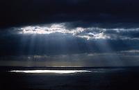 Shafts of light penetrating through storm clouds over the sea. Tenerife, Canary Islands.