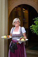 Germany, Bavaria, Lower Franconia, Sommerach near Volkach: Franconian wine village - Hotel and vineyard 'Zum Weissen Lamm', friendly waitress serving local speciality 'Schaeufele with Knoedel (dumpling) | Deutschland, Bayern, Unterfranken, bei Volkach, Sommerach: fraenkischer Weinort an der suedlichen Mainschleife auf der Weininsel - Gasthof, Hotel und Weingut Zum Weissen Lamm,  eine herzliche Kellnerin serviert Schaeufele mit Knoedel