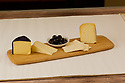 Cheese tasting platter with three cheeses, crackers and olives on a cutting board