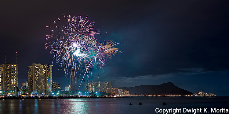 Weekly fireworks display in Waikiki with Diamond Head standing sentry. Full moon behind clouds adds the lighting that brings Diamond Head into relief.