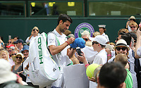 Novak Djokovic (SRB) signs autographs after winning his match against Philipp Kohlschreiber (GER) in their Gentleman's Singles First Round match<br /> <br /> Photographer Rob Newell/CameraSport<br /> <br /> Wimbledon Lawn Tennis Championships - Day 1 - Monday 1st July 2019 -  All England Lawn Tennis and Croquet Club - Wimbledon - London - England<br /> <br /> World Copyright © 2019 CameraSport. All rights reserved. 43 Linden Ave. Countesthorpe. Leicester. England. LE8 5PG - Tel: +44 (0) 116 277 4147 - admin@camerasport.com - www.camerasport.com