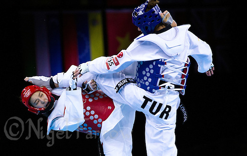 10 AUG 2012 - LONDON, GBR - Hwang Kyung-Seon (KOR) (left) of South Korea and Nur Tatar (TUR) (right) of Turkey both land kicks during the women's -67kg category final at the London 2012 Olympic Games Taekwondo at Excel in London, Great Britain .(PHOTO (C) 2012 NIGEL FARROW)