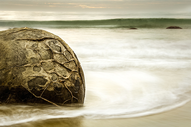 Moeraki Boulder surrounded by waves, coastal Otago. <br /> <br /> South Island, New Zealand - stock photo, canvas, fine art print