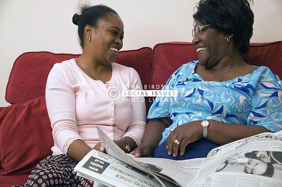 Mother and daughter reading the newspaper together at home; smiling,