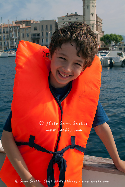Young boy wearing a life jacket on board a boat, La Ciotat, Provence, France.