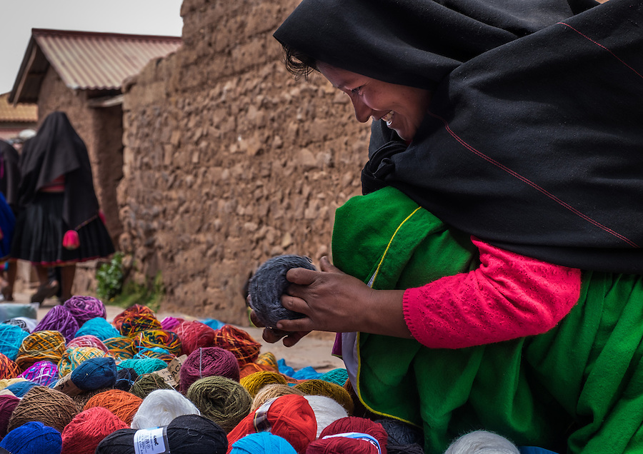 TAQUILE, PERU - CIRCA OCTOBER 2015:  A woman from the insland of Taquile buying wool in the market of Taquile in Lake Titicaca.