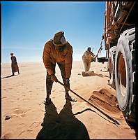 Sahara desert, Libya-Chad, November/December 2004..Every week, a convoy of 40 privately owned Libyan trucks loaded by the WFP with about 1000 metric tons of western food aid cross 2500 km of deep desert across Libya and Chad to reach more than 200 000 refugees from Darfur in camps near the Sudanese border. The heavily loaded trucks sink heavily in the soft sand.