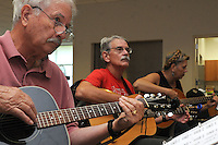 NWA Democrat-Gazette/FLIP PUTTHOFF<br /> Guitar students John Yount (from left) Grimsley Graham and Dianna Mair play during guitar lessons on Tuesday April 18 2015 at the Adult Wellness Center in Rogers. About a dozen students are enrolled in lessons at the center. A picking circle is at 1 p.m. each Tuesday and is open to any guitar players who want to play and sing.