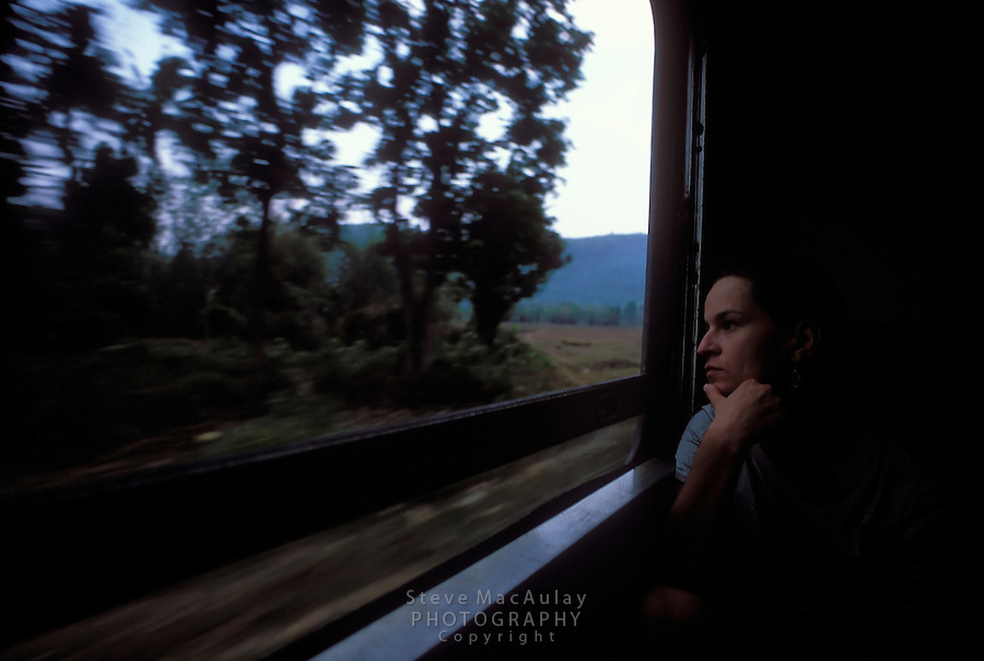 Female traveler looking contempaltive, looking out window of speeding train, Thailand