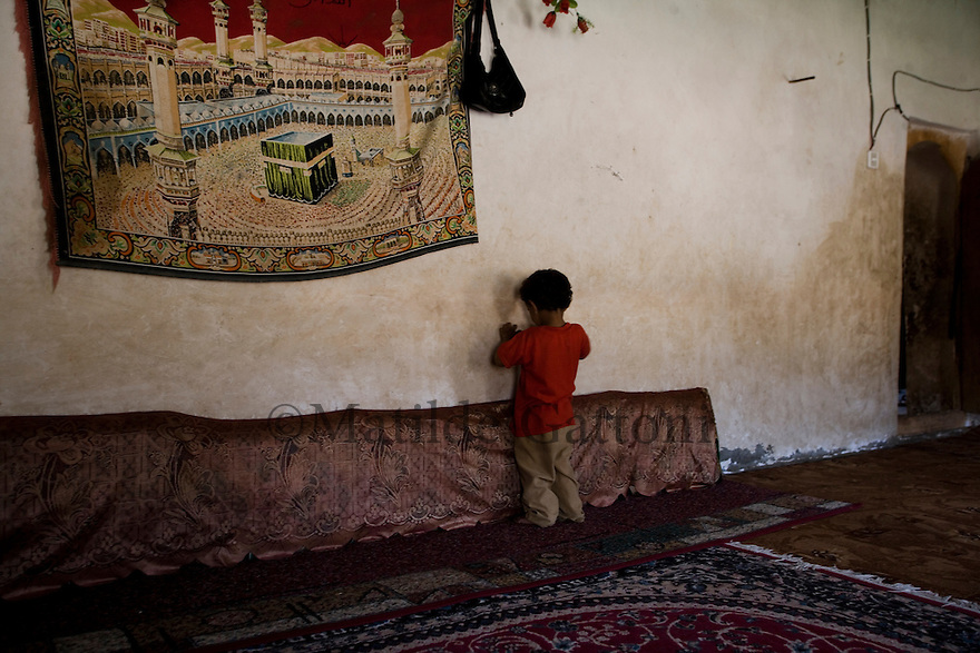 Yemen - Little boy standing in his house next to the carpet represening Mecca. Yemen's economy depends heavily on oil production, and its government receives the vast majority of its revenue from oil taxes. Yet analysts predict that the country's petroleum output, which has declined over the last seven years, will fall to zero by 2017. The government has done little to plan for its post-oil future. Yemen's population, already the poorest on the Arabian peninsula and with an unemployment rate of 35%, is expected to double by 2035..The trends will exacerbated large and growing environmental problems, including the exhaustion of Yemen's groundwater resources. Given that a full 90% of the country's water is used for agriculture, this trend portends disaster..Sanaa's well are expected to dry out by 2015, partly due to illegal drilling, partly because 40% of the city's water is diverted for qat production, and partly because conservation rules are difficult to enforce. Only 20% of the houses receive water, the other 80% has to collect it from pumps and wells. 15% of the urban population only uses bottled water as its primary drinking water source and that is why Yemen has one of the highest world mortality rate, most of the diseases being related to water.