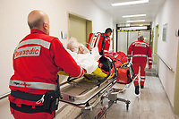 "Switzerland. Canton Ticino. Lugano. Ospedale Civico. The Rega has rescued an elderly man lying on a stretcher and suffering from a heart problem. The Rega crew (Left to right: the paramedic Paolo Menghetti, the Doctor Michele Musiari and the pilot Corrado Sasselli ) push a stretcher on their way to the emergency room. All Rega helicopters carry a crew of three: a pilot, an emergency physician, and a paramedic who is also trained to assist the pilot for radio communication, navigation, terrain/object avoidance, and winch operations. (Left to right) Damiano Salmina is the doctor, Mario Agustini the pilot and Giovanni Beldi the paramedic. The name Rega was created by combining letters from the name ""Swiss Air Rescue Guard"" as it was written in German (Schweizerische Rettungsflugwacht), French (Garde Aérienne Suisse de Sauvetage), and Italian (Guardia Aerea Svizzera di Soccorso). Rega is a private, non-profit air rescue service that provides emergency medical assistance in Switzerland. Rega mainly assists with mountain rescues, though it will also operate in other terrains when needed, most notably during life-threatening emergencies. As a non-profit foundation, Rega does not receive financial assistance from any government. 10.09.2017 © 2017 Didier Ruef"