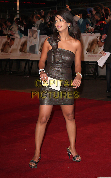 """KONNIE HUQ.At the UK Film Premiere of """"Revolutionary Road"""" at the Odeon Leicester Square, London, England, January 18th 2009..full length one shoulder bow dress brown sparkly shiny white clutch bag sandals .CAP/ROS.©Steve Ross/Capital Pictures"""
