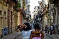 Young Cuban girls walk embraced down the street during the dusk in the Havana downtown, Cuba, 11 August 2008. About 50 years after the national rebellion, led by Fidel Castro, and adopting the communist ideology shortly after the victory, the Caribbean island of Cuba is the only country in Americas having the communist political system. Although the Cuban state-controlled economy has never been developed enough to allow Cubans living in social conditions similar to the US or to Europe, mostly middle-age and older Cubans still support the Castro Brothers' regime and the idea of the Cuban Revolution. Since the 1990s Cuba struggles with chronic economic crisis and mainly young Cubans call for the economic changes.