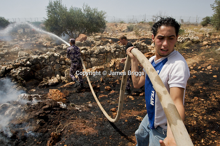 Shabab (Palestinian youths) assist Palestinian Civil Defence Officers in extinguishing fires caused after the IDF fired CS gas canisters which landed in dry undergrowth during a demonstration against Israel's controversial West Bank barrier in the village of Bil'in near Ramallah on 04/06/2010.