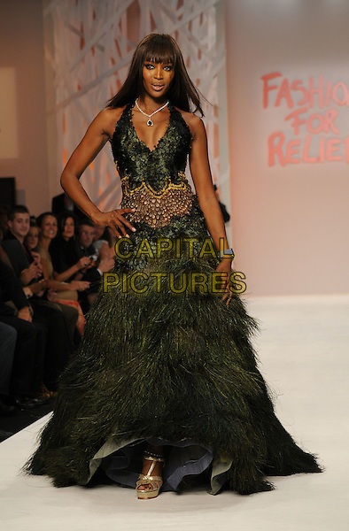 NAOMI CAMPBELL .LFW Fashion For Relief fundraiser, BFC Tent, Natural History Museum, London, England..September 17th, 2008.week full length catwalk dress black green feathers hand on hip black belt layers layered halterneck .CAP/CAN.©Can Nguyen/Capital Pictures.