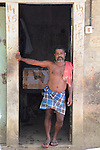 A man shelters from the hot sun in his doorway. He is one of the few remaining men in his village.  Most have left in search of higher wages in the Middle East.